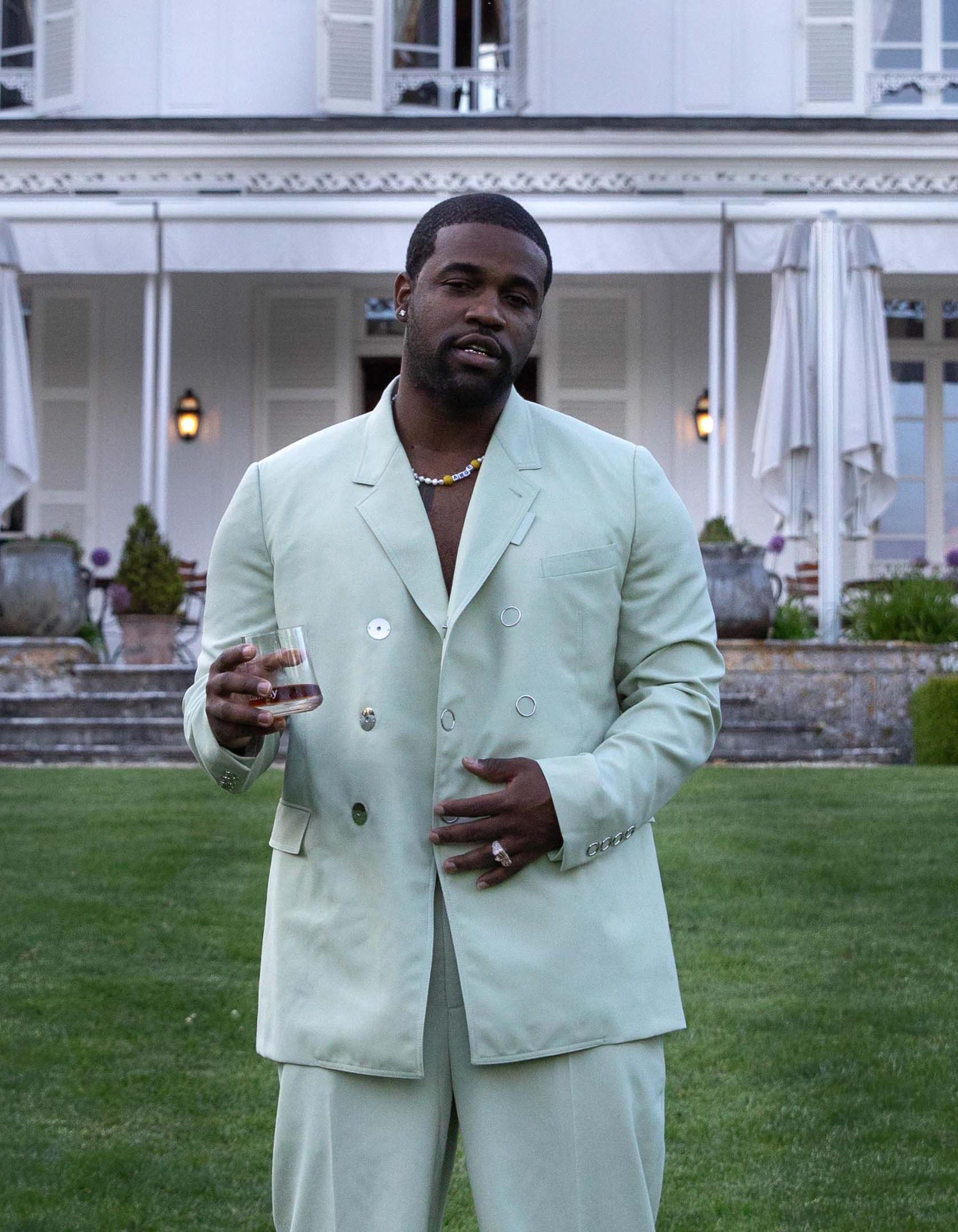 ASAP Ferg standing in front of the Hennessy Maison in Cognac, France, with a glass of Hennessy V.S neat in his hand.