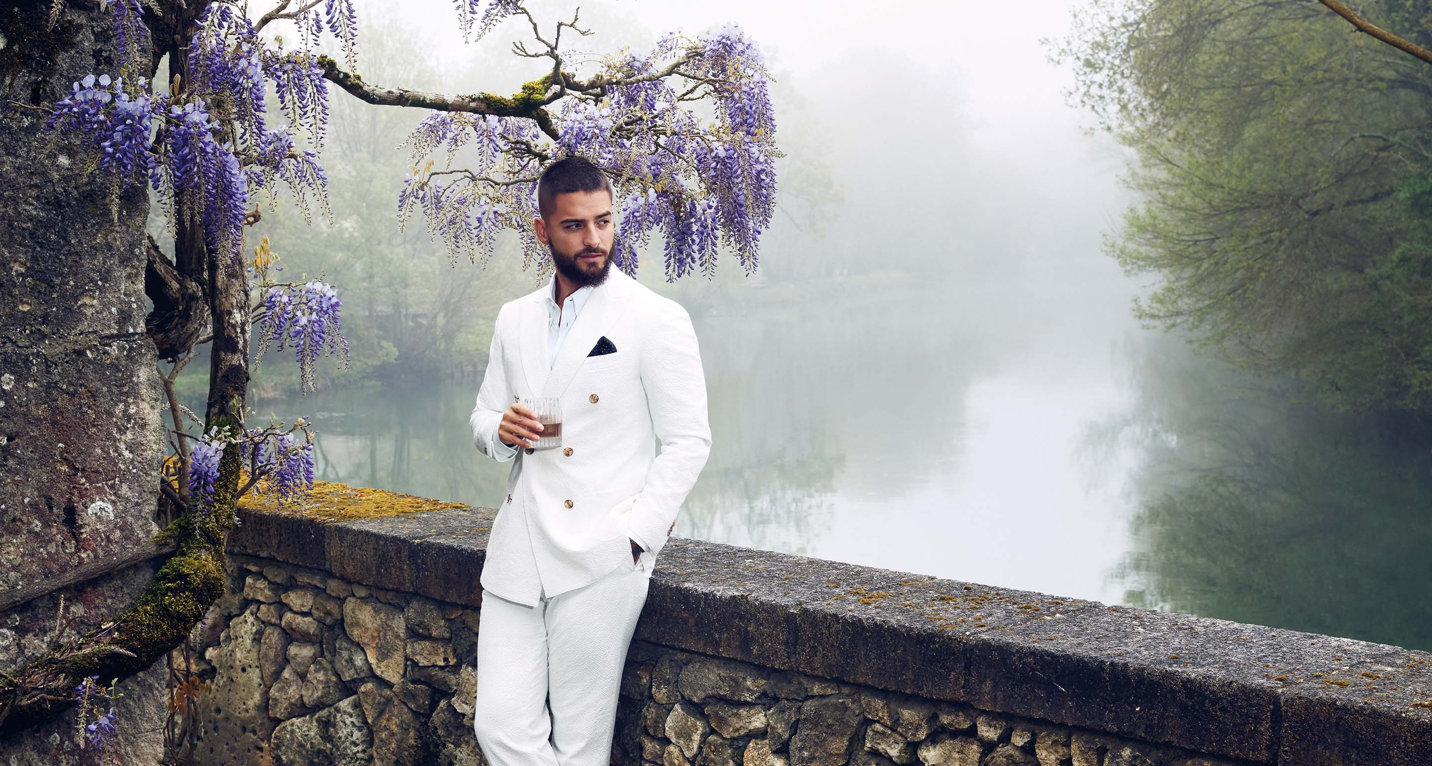 Award-winning musician Maluma with a Hennessy cocktail in his hand, wearing a white suit standing in front of a Wisteria tree and leaning against a stone ledge.